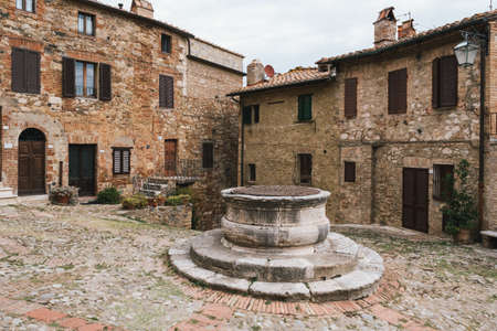 Castiglione d'Orcia Town Center with an Old Well and Cobblestones in Tuscany, Italy and Stone Houses
