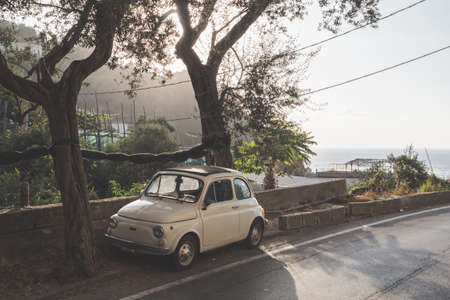 Massa Lubrense, Italy - August 23 2020: Retro, Vintage Fiat Nuova 500 Cinquecento Car in Beige or Ivory parked on the Sorrentine Coast in Summer