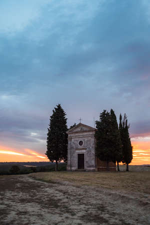 Chapel Capella della Madonna di Vitaleta in Val d' Orcia, Tuscany, Italy at Sunrise or Dawn in the Romantic and Mysterious First Light in the Early Morning with Cypress Trees