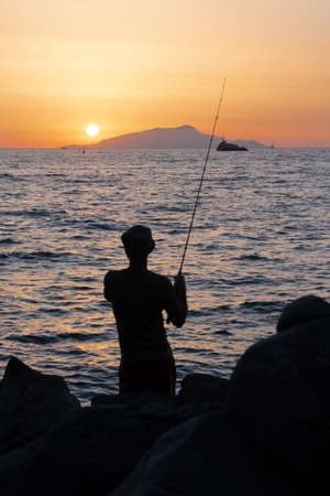 Fisherman or Angler on the Sorrentine Coast or Peninsula in the Sunset across from Ischia at Dusk Reklamní fotografie