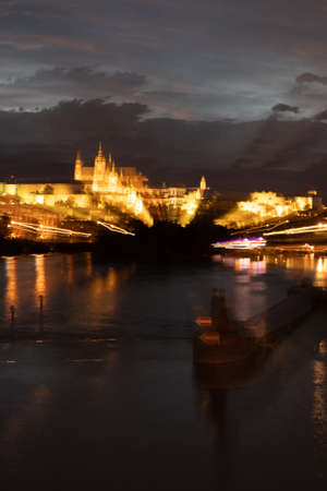 Psychedelic, Blurred Cityscape of Prague at Illuminated at Night with River Vltava and Saint Vitus Cathedral