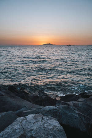 Sunset behing Ischia Island on the Sorrento Coast in Italy with Rocks and the Tyrrhenian Sea Coast