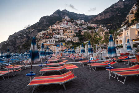 Positano, Italy - August 24 2020: Positano Spiaggia Beach with Orange Beach Chairs and Umbrellas in the Evening with View of the Village Redakční