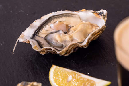 Raw Oyster and Stout with a Lemon Wedge, an Irish Cuisine Speciality