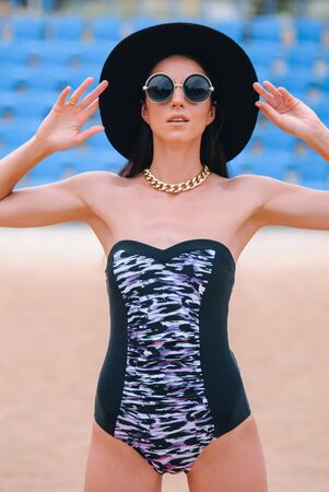 Woman dressed in a swimsuit, hat sunglasses and accessories