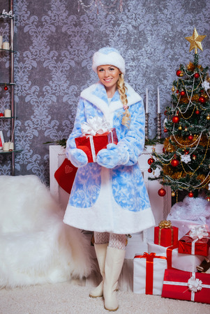 Beautiful Russian Blondie Girl Dressed as Snow Maiden (Snegurochka) with Gifts near a Christmas Tree and Fireplace 版權商用圖片