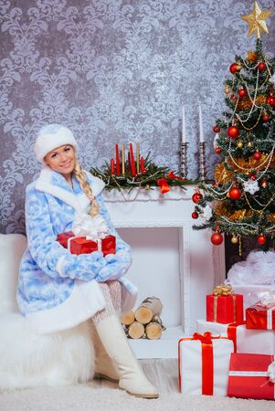 Beautiful Russian Blondie Girl (Snegurochka) with Gifts under the Cristmas tree and Fireplace