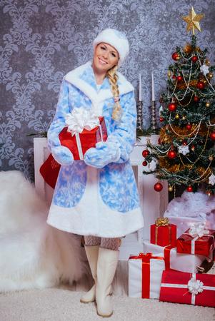 Beautiful Russian Snegurochka Sits Gifts near a Christmas Tree and Fireplace