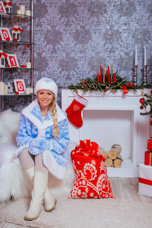 Beautiful Russian Blondie Girl Dressed as Snow Maiden (Snegurochka) Sits with Gifts near the Fireplace