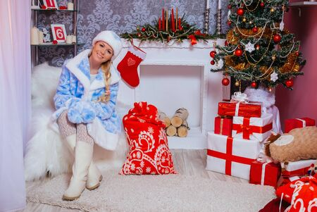 Beautiful Russian Blondie Girl Dressed as Snow Maiden (Snegurochka) Sits with Gifts near a Christmas Tree and Fireplace