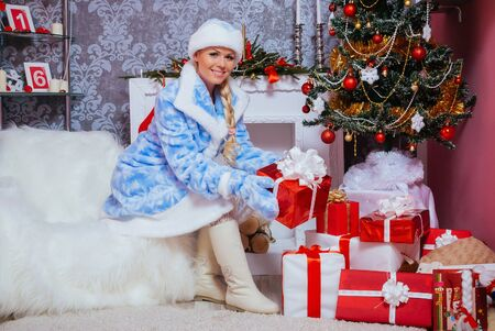 Beautiful Russian Blondie Girl Dressed as Snow Maiden (Snegurochka) Sits with presents near a Christmas Tree and Fireplace
