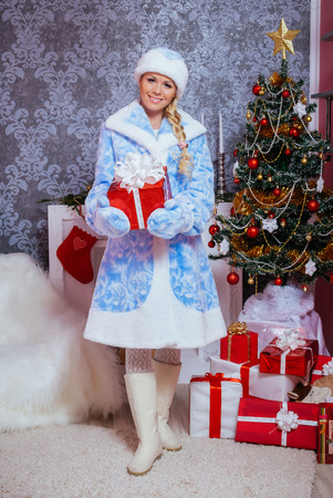 snegurochka: Beautiful Russian Blondie Girl Dressed as Snow Maiden (Snegurochka) with Gifts near a Christmas Tree and Fireplace Stock Photo