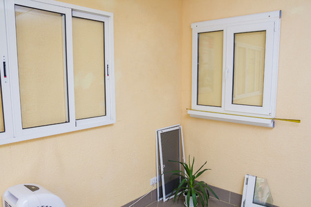 tempered: Several samples of plastic windows on the wall, ready to install. Stock Photo