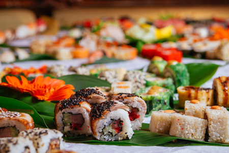 A variety of sushi and maki rolls sitting served on the table