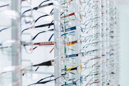 Set of eyeglass frames in the optics store. Close-up showing many eyeglasses in background.