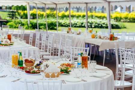 Holiday table under the white tent. White banquet with wedding or party tent
