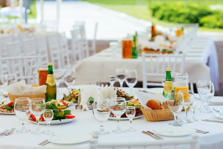Served for outdoor holiday banquet table with dishes, snack, cutlery, and water glasses. 版權商用圖片