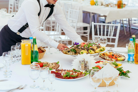 Waiter in uniform served table for a banquet