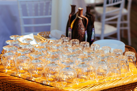Close-up of empty glasses for brandy and whiskey, stemware on wicker table