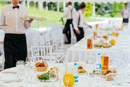 Waiters in uniform served tables for a banquet