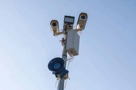 Surveillance CCTV security cameras on blue sky background with megaphone