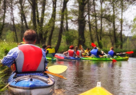 Tourists kayaking on river in forest
