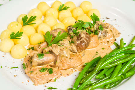 Pork tenderloin with potatoes and wild mushroom sauce and green beans on white plate. Close up.