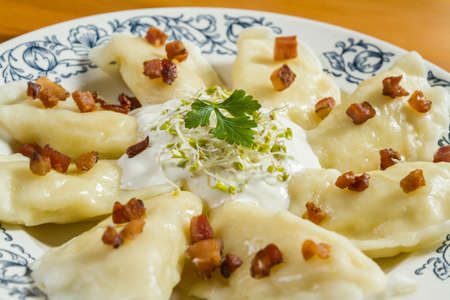 nudelholz: Cooked dumplings with cheese pork scratching and creme fraiche on wooden table. Polish, ukrainian, russian traditional food.