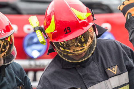 rescuing: ZAMOSCPOLAND -AUGUST 13,2017: Firefighters working on an auto vehicle extrication with a hydraulic power rescue tool Editorial