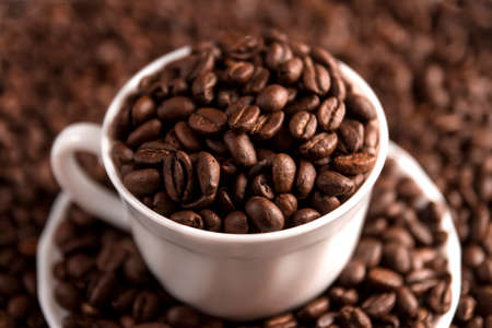Cup filled with coffee beans on coffee beans background. Selective focus. Stock Photo