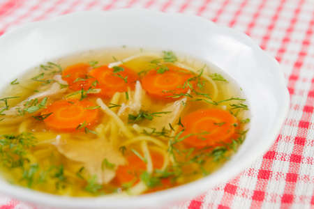 Chicken soup or broth with noodels, chicken meat pieces , carrot slices and herbs in white bowl. Фото со стока