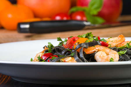 Black squid ink Fettuccine pasta with prawns or shrimps cherry tomatoes, parsley, chili in wine and butter sauce.