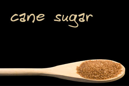 cane sugar on wooden spoon isolated on black background