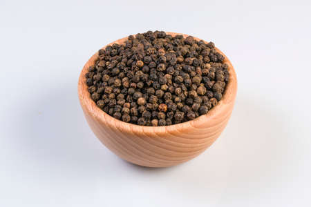 Black pepper peppercorns in wooden bowl isolated on white background. Closeup.