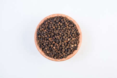 Black pepper peppercorns in wooden bowl isolated on white background. Top view.
