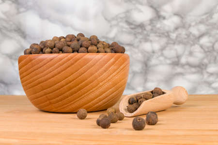 Allspices or Jamaica pepper in wooden scoop and bowl on bamboo desk. Closeup Banque d'images