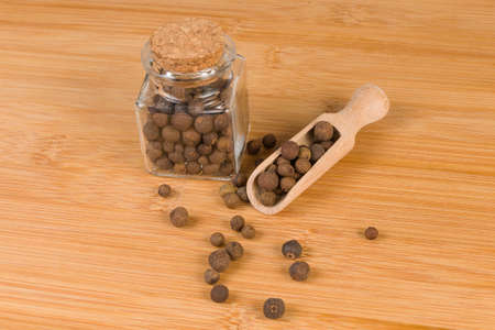 Allspices or Jamaica pepper in wooden scoop and jar on bamboo desk. Closeup.