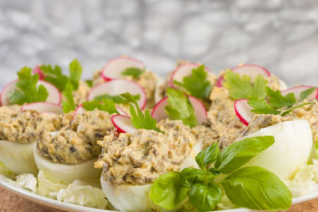 Boiled eggs stuffed with champignon mushrooms and sliced radish, parsley, salad on white plate.
