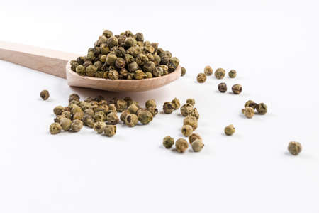 green pepper peppercorns  in wooden spoon isolated on white background. Stok Fotoğraf