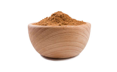 milled or ground nutmeg in wooden bowl isolated on white background. Spices and food ingredients.