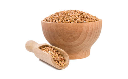 roasted buckwheat in wooden bowl and scoop isolated on white background. nutrition. bio. natural food ingredient.front view.