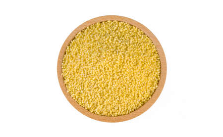 millet groats in wooden bowl isolated on white background. nutrition. food ingredient.