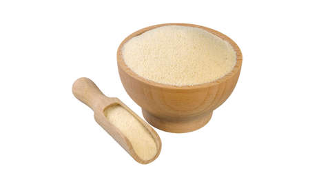 semolina in wooden bowl and scoop isolated on white background. nutrition. bio. natural food ingredient.