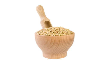 raw buckwheat in wooden bowl and scoop isolated on white background.