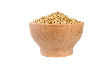 raw buckwheat in wooden bowl isolated on white background.