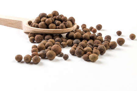 Allspice or Jamaican pepper on wooden spoon on white background