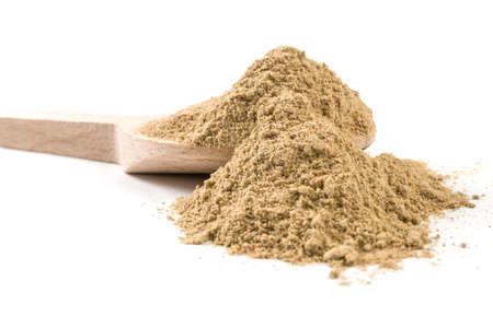 cardamon powder on wooden spoon on white background Zdjęcie Seryjne
