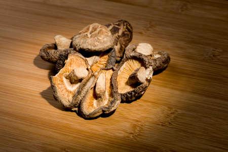 group of dried Shitake mushrooms laying on bamboo desk. food ingredient.