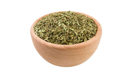 tarragon herb in wooden bowl isolated on white background. 45 degree view. Spices and food ingredients. Stock Photo