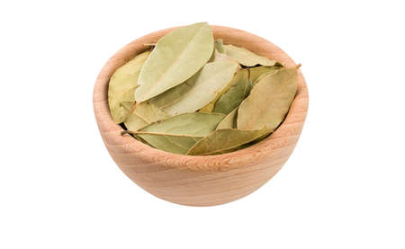 bay leaves in wooden bowl isolated on white background. 45 degree view. Spices and food ingredients. Stock Photo